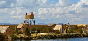 LAKE TITICACA, PERU - AUGUST 3: Uros Indian woman looking out from a watchtower on a reed island in Lake Titicaca August 3, 2013.